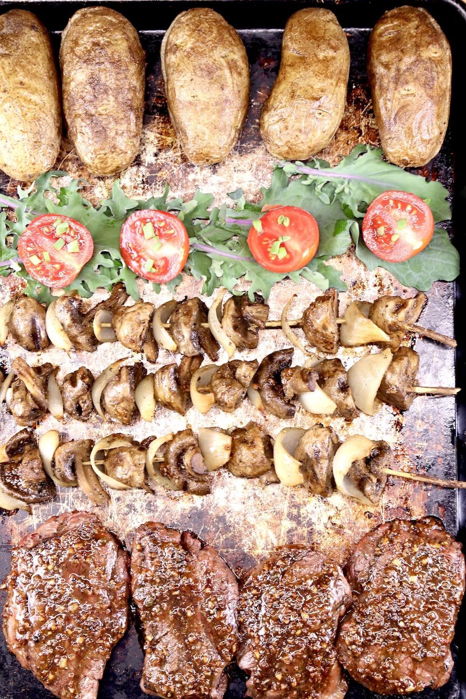 Sheet pan with baked potatoes, lettuce & tomatoes, mushroom skewers and grilled steaks