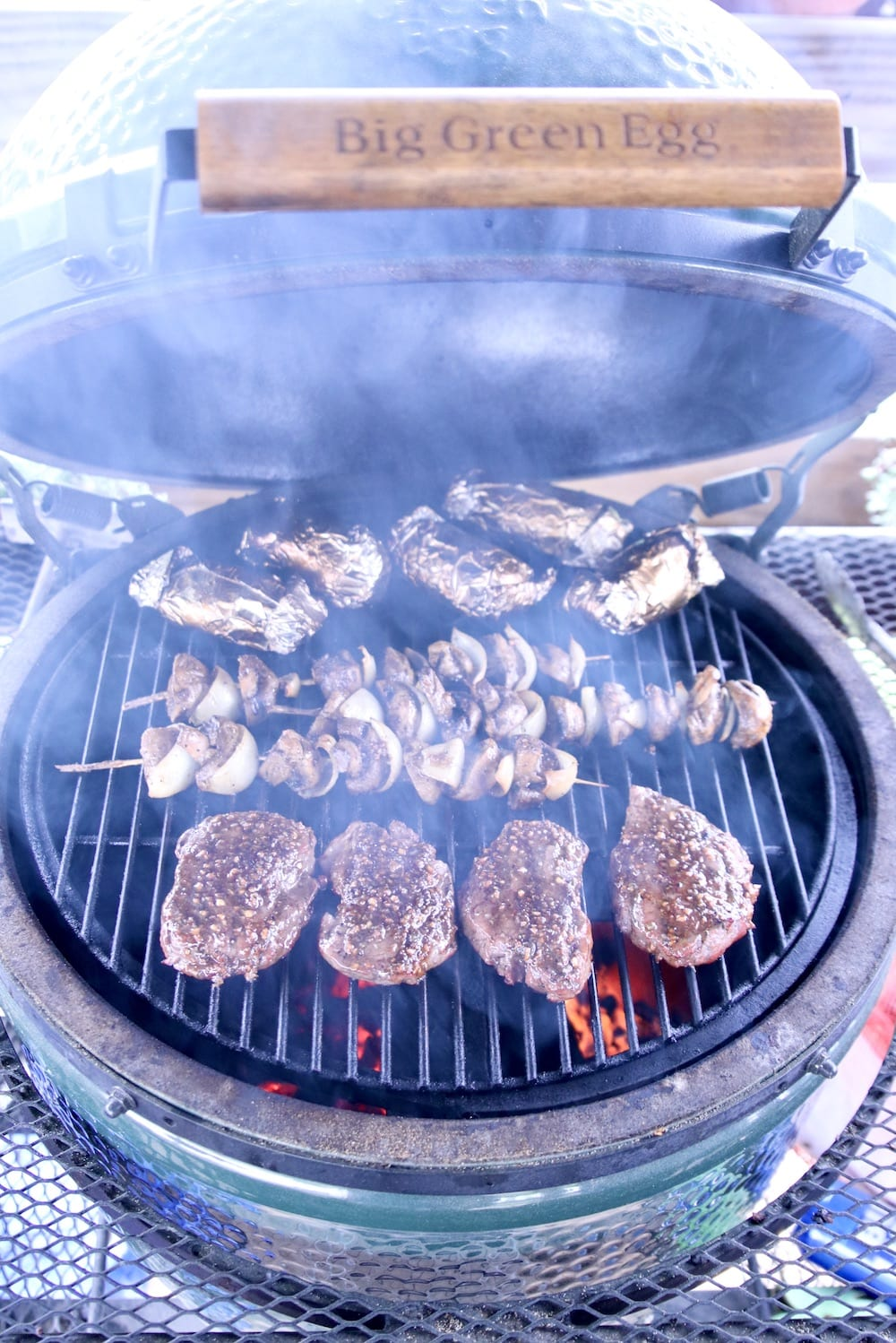 big green egg grill with steaks, mushrooms and foil wrapped potatoes