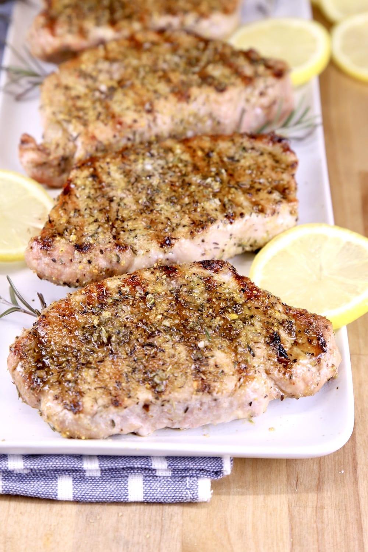 Grilled pork chops on a platter with lemon slices