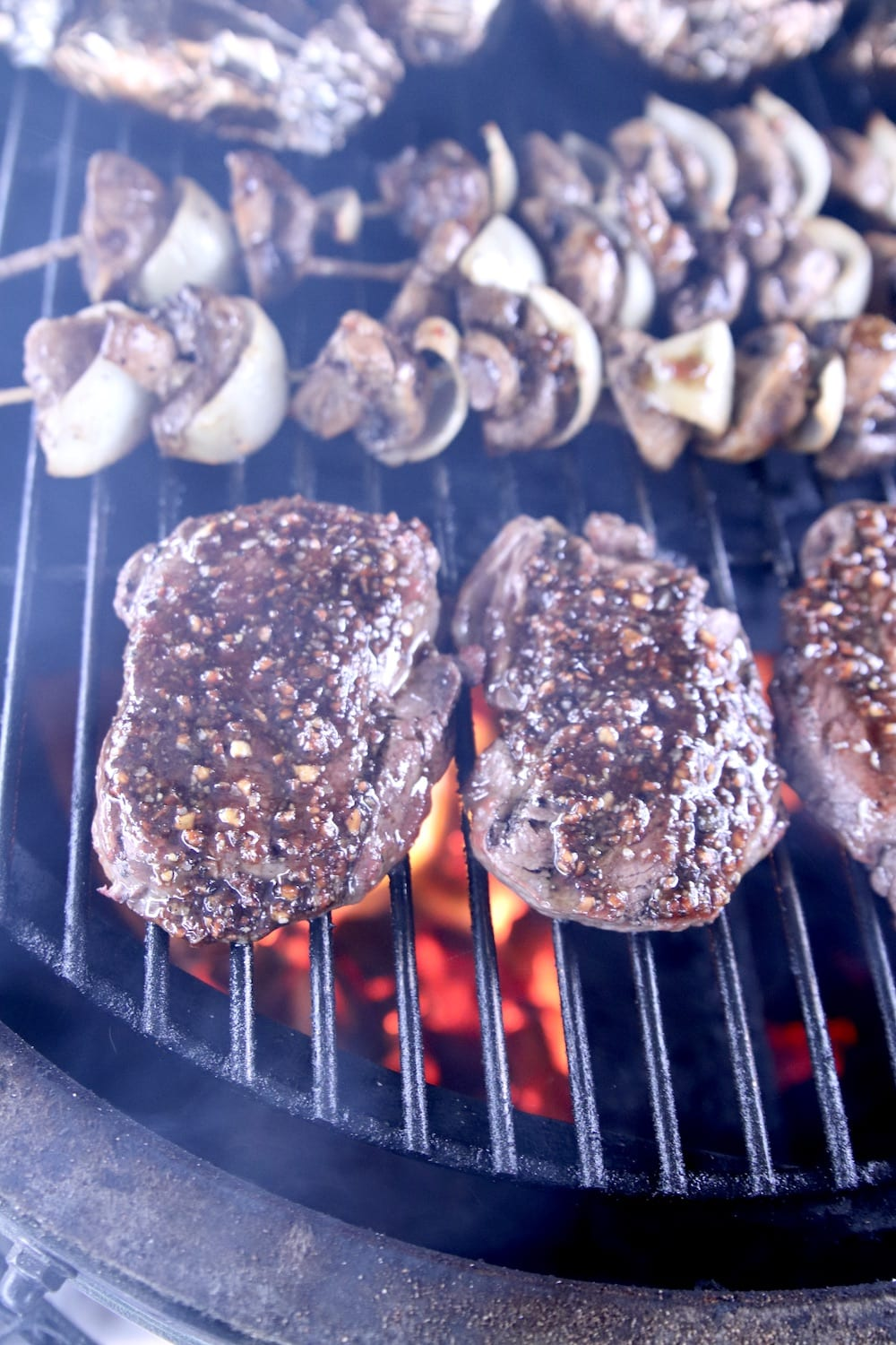 Steaks, mushroom skewers and foil wrapped potatoes on a grill