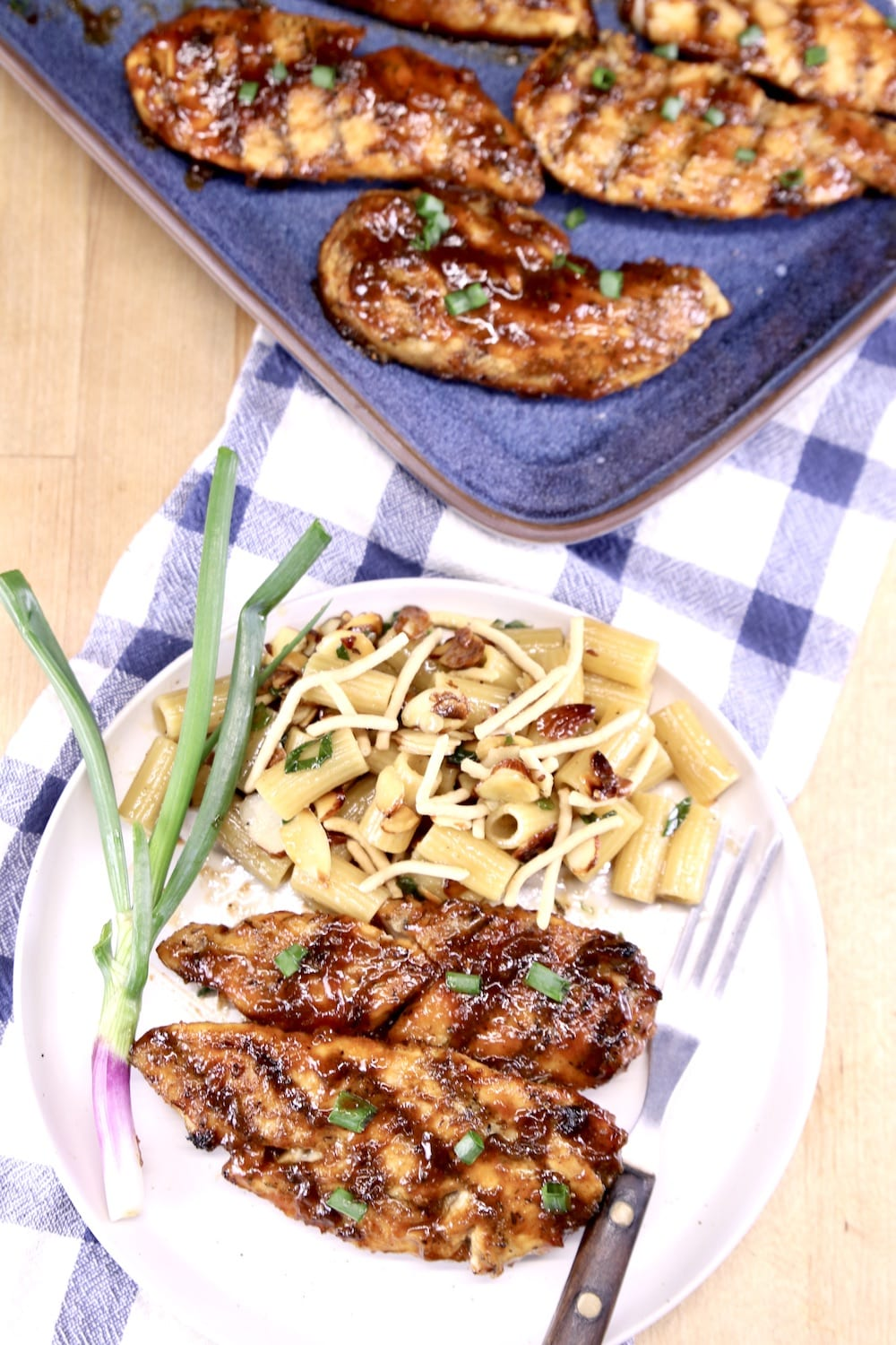 Grilled Chicken Tenders on a plate with pasta and a green onion