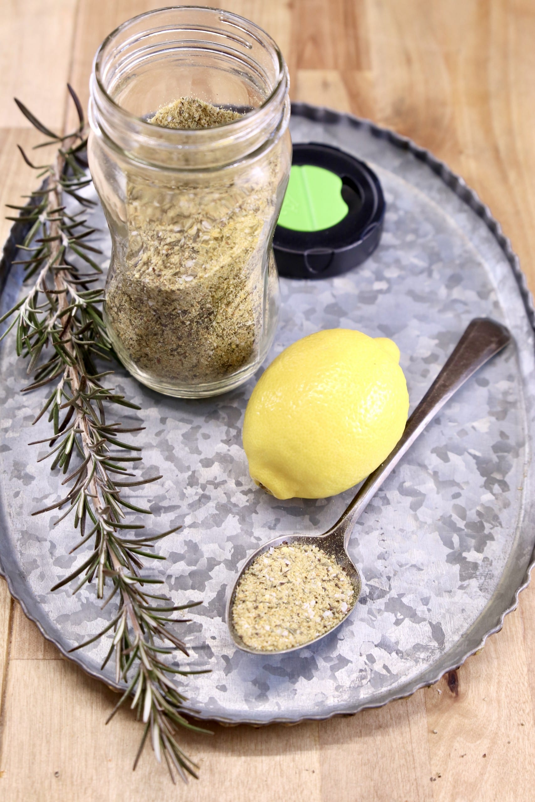 lemon and rosemary dry rub for grilling on a tray with fresh lemon and sprig of rosemary