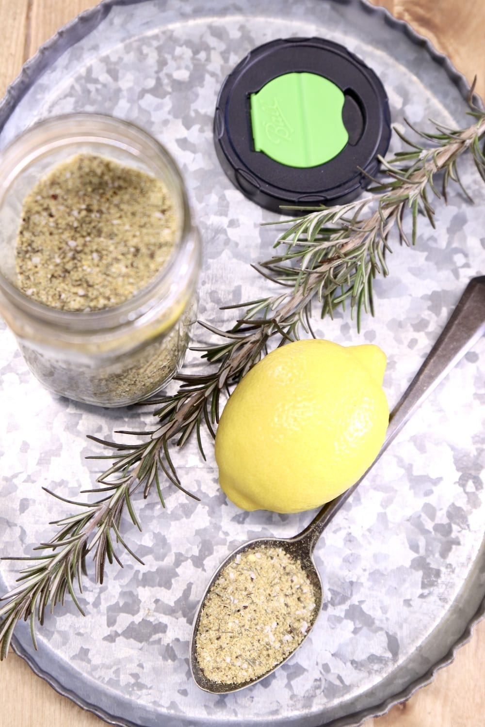 overhead of tray with lemon and rosemary dry rub. Whole lemon, jar of spices and sprig of rosemary