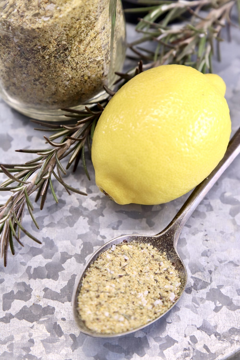 lemon rosemary dry rub on a spoon on a tray with whole lemon, rosemary sprig, jar of spices