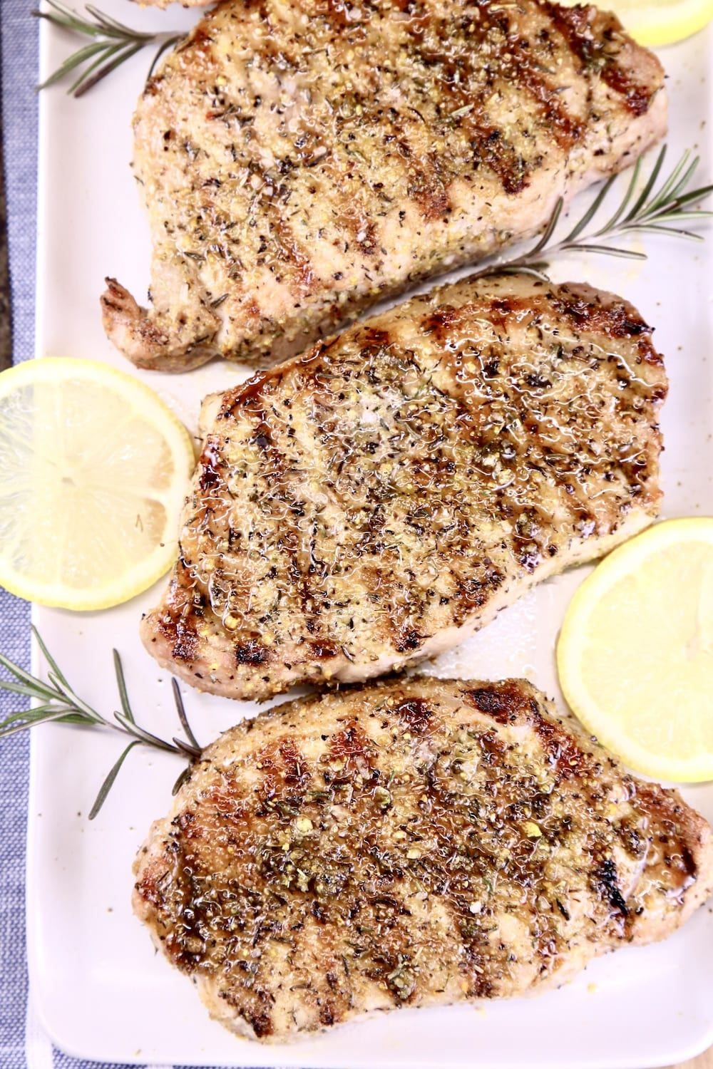 grilled pork chops on a platter with lemon slices and rosemary sprigs