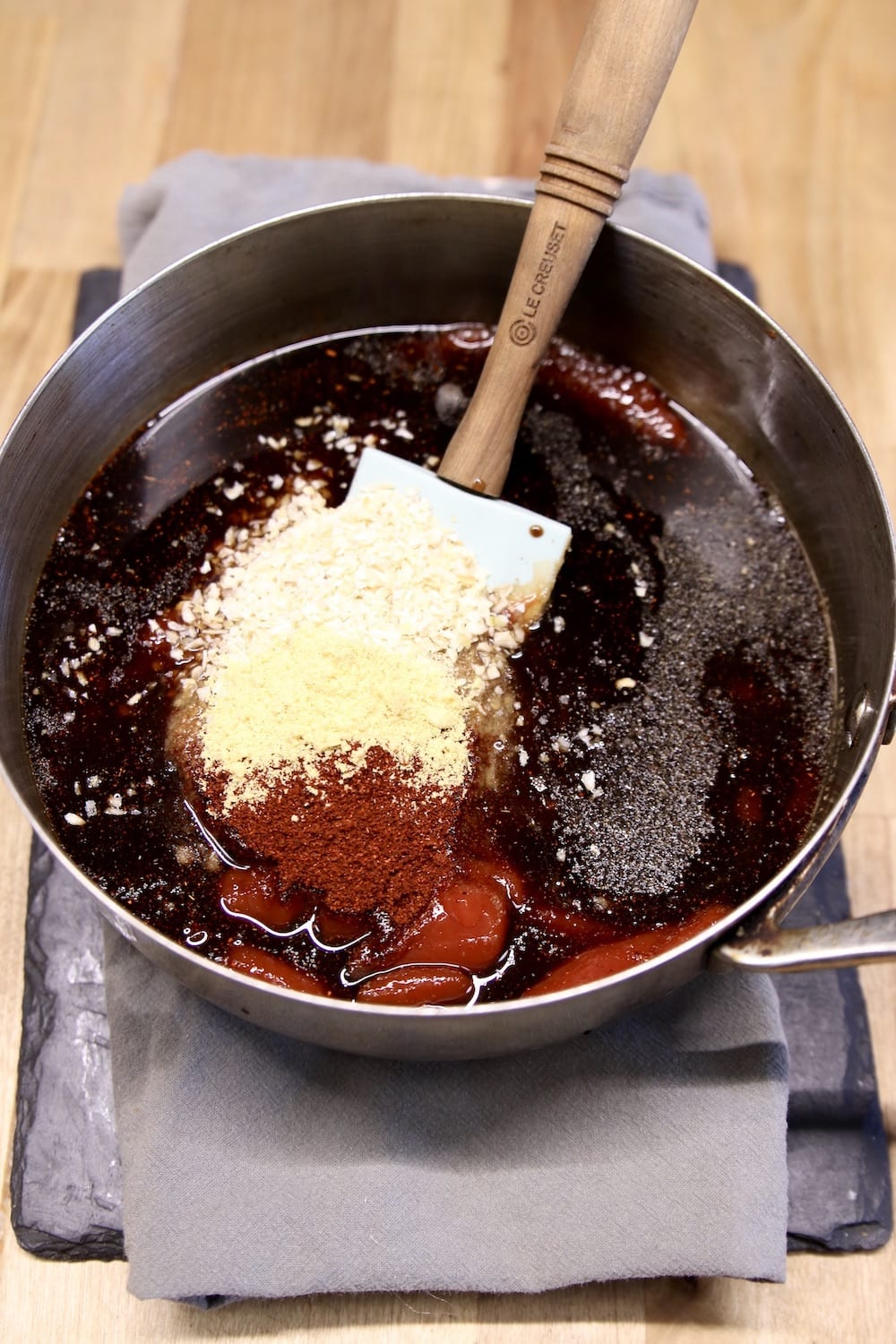 Ketchup, worcestershire sauce, spices in a pan with a spatula