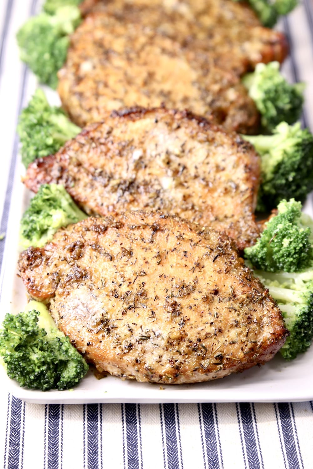 Onion Thyme Grilled Pork chops on a platter with broccoli spears