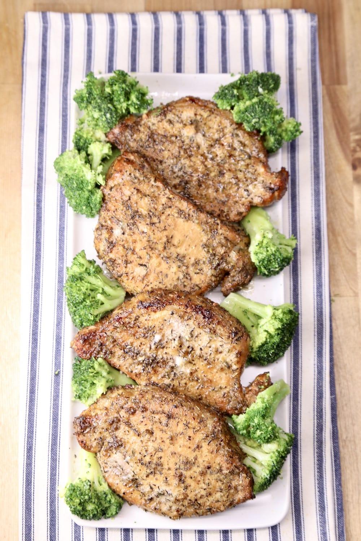 4 grilled pork chops with broccoli on a rectangle platter, blue stripe towel under platter