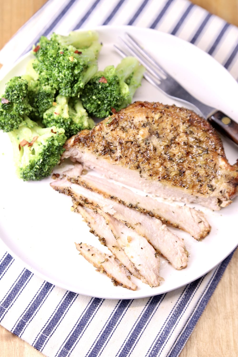 grilled pork chop on a plate with broccoli