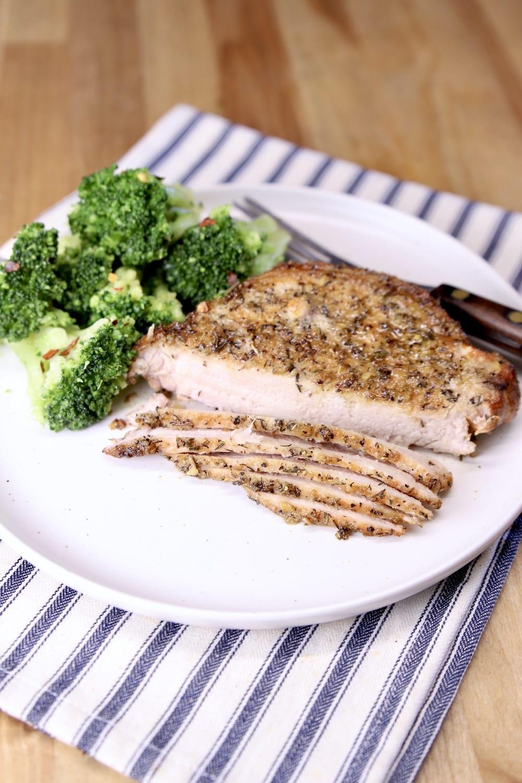 plate with pork chop, partially sliced, broccoli
