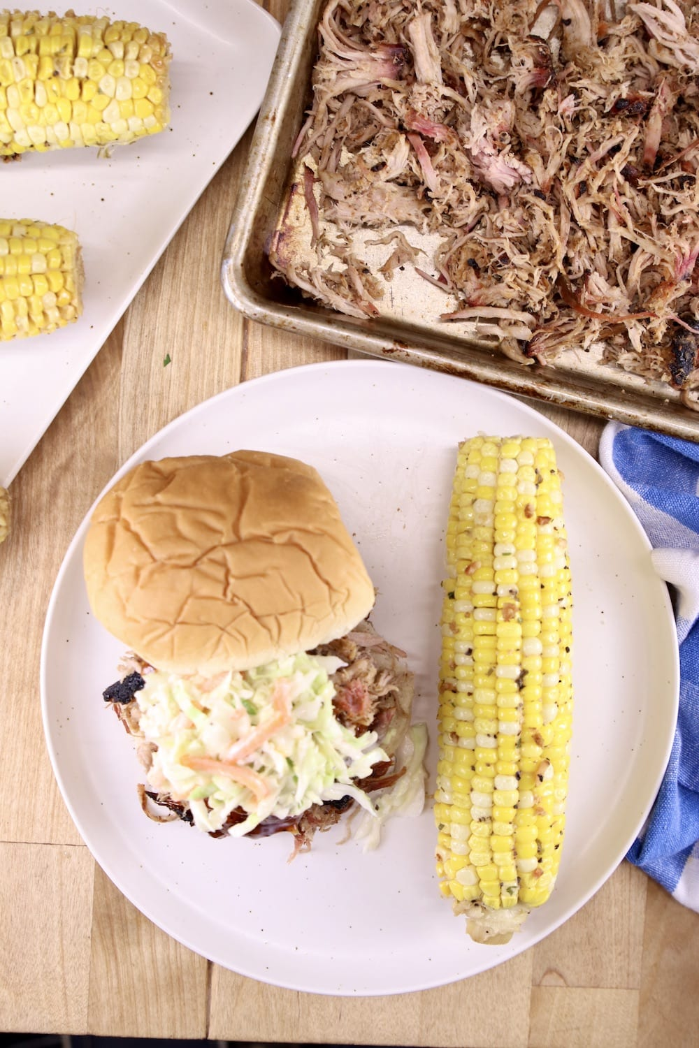 pulled pork on a tray and plated on a sandwich with coleslaw served with corn on the cob