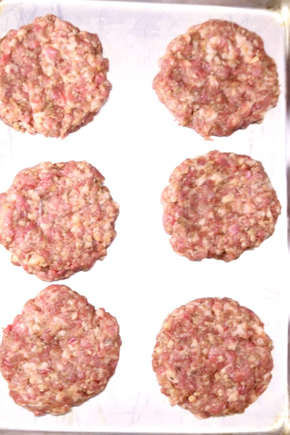 6 burger patties on a baking sheet ready to grill