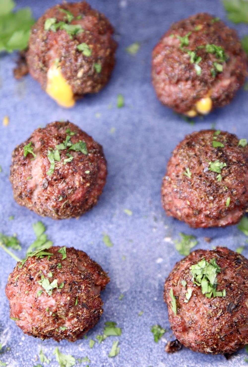 Cheddar stuffed meatballs on a blue platter