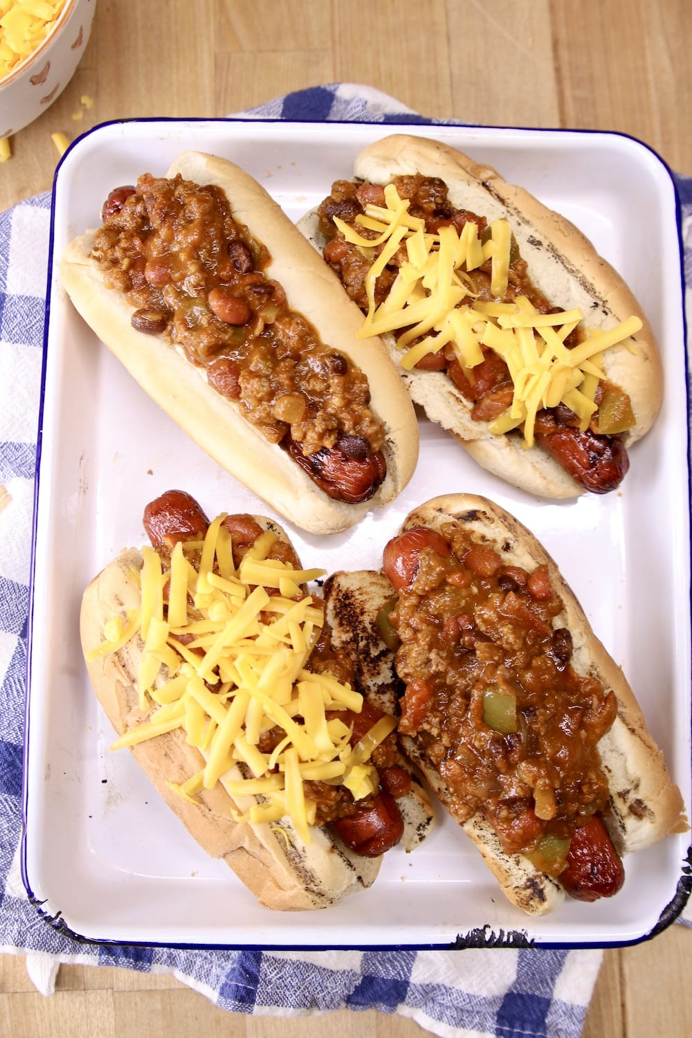 4 hot dogs in a pan, covered with chili and cheese