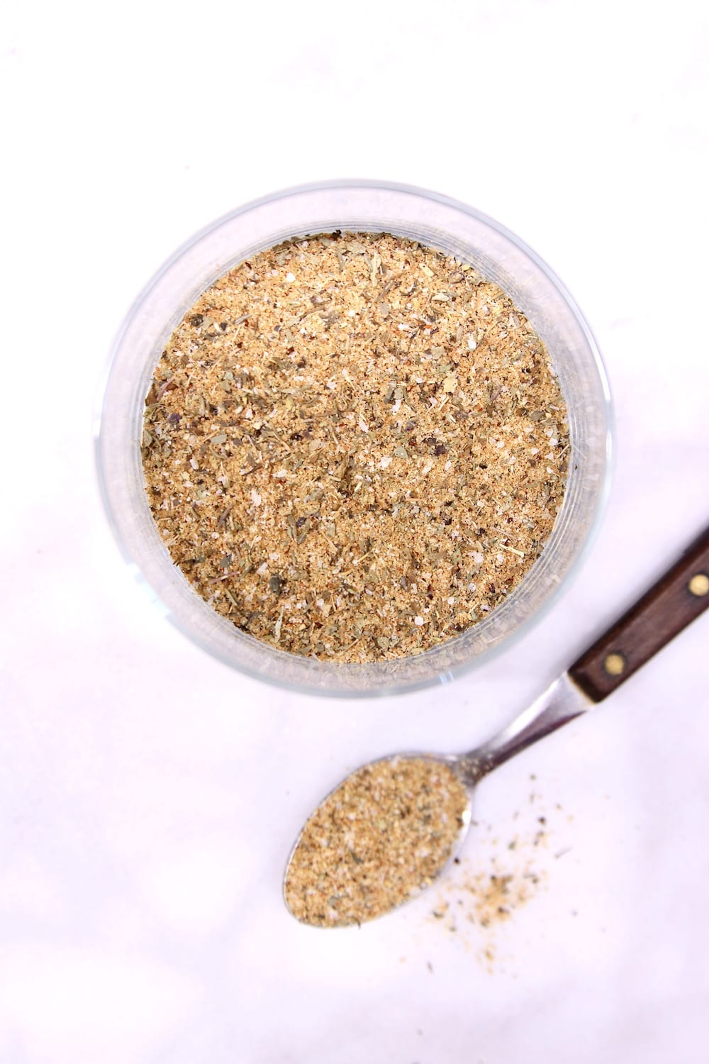 Garlic and Herb Dry Rub in a jar with a spoonful next to the jar