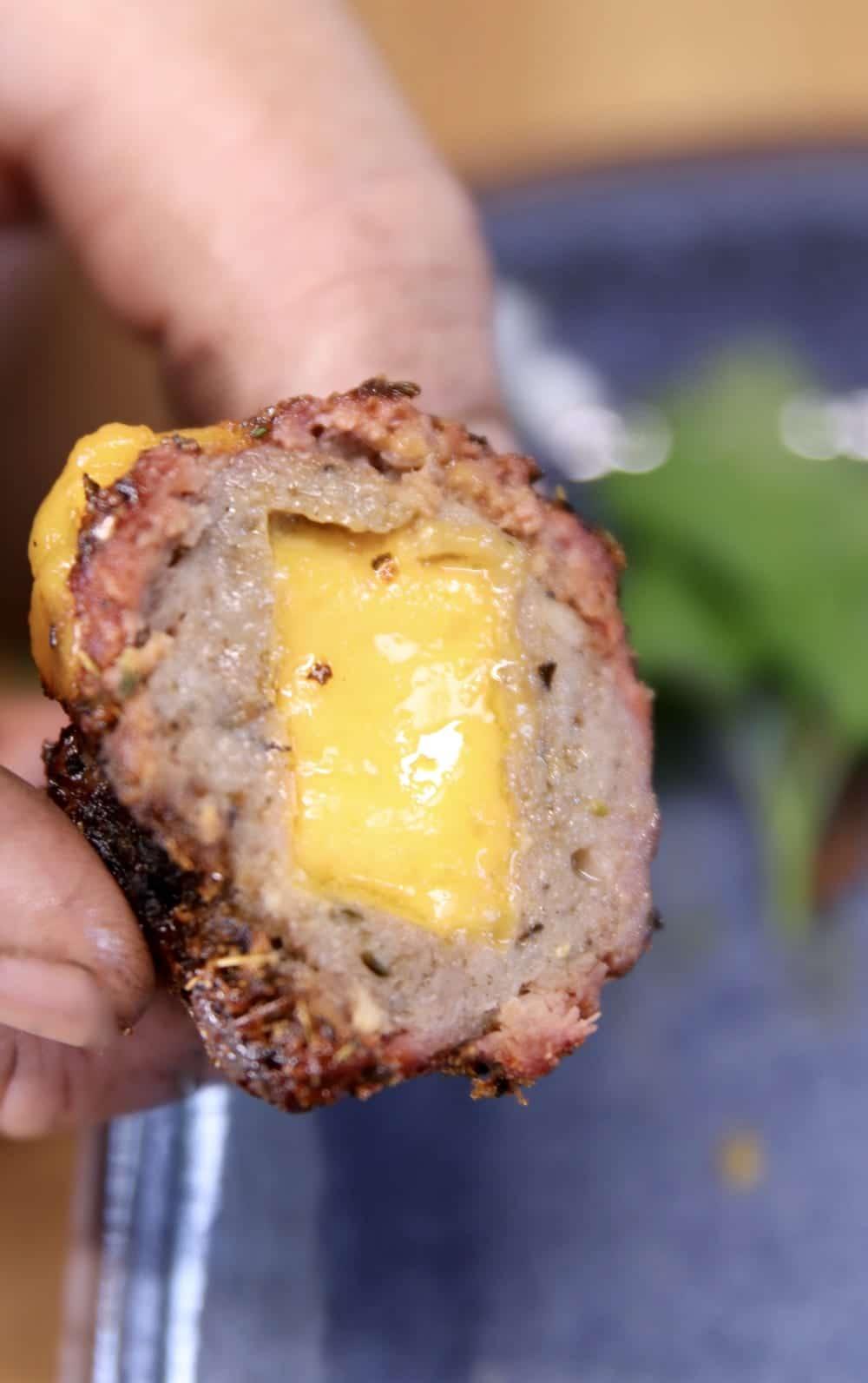 Cheddar stuffed meatball, cut in half, close up