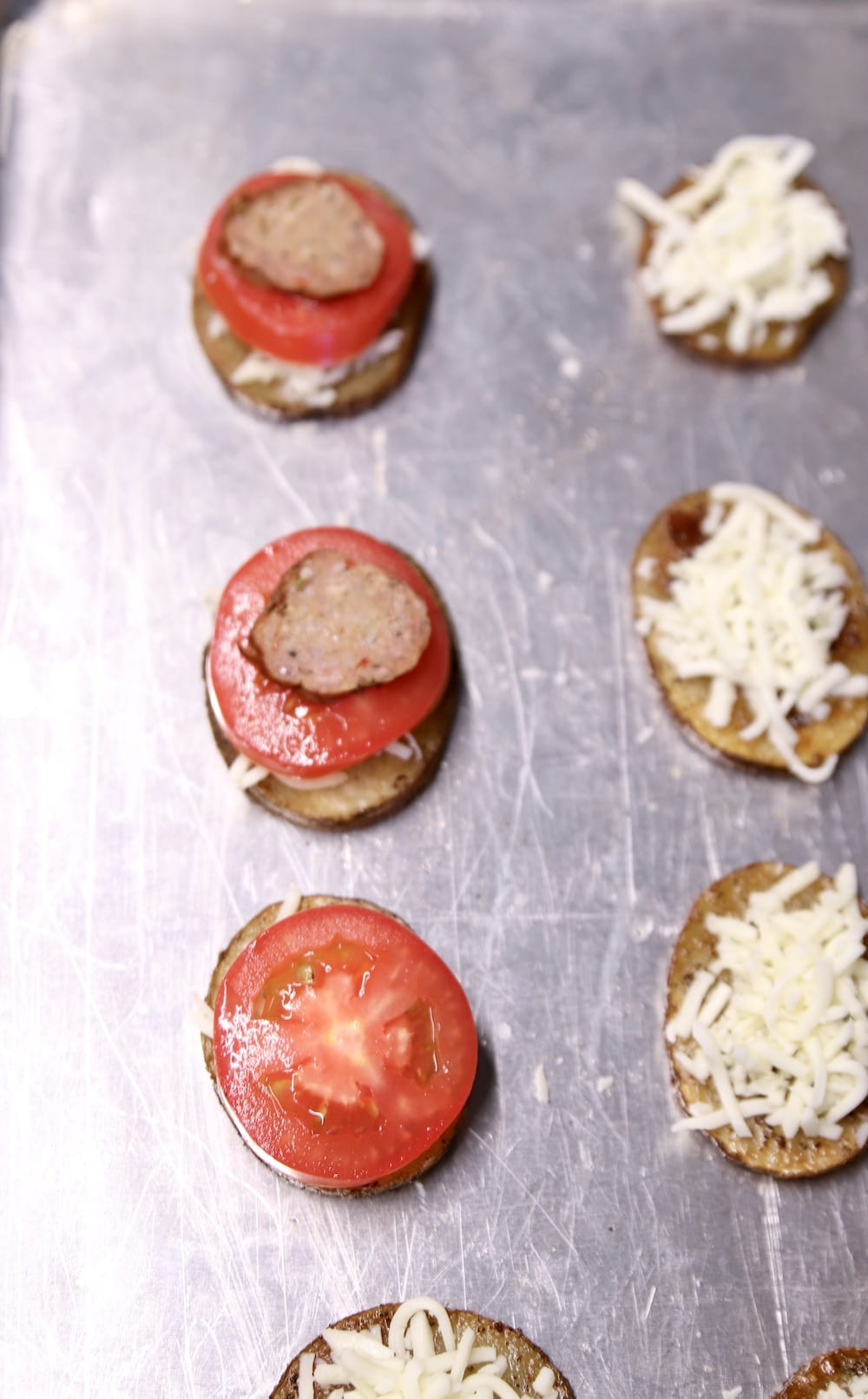 topping potato rounds with tomato slices and smoked sausage