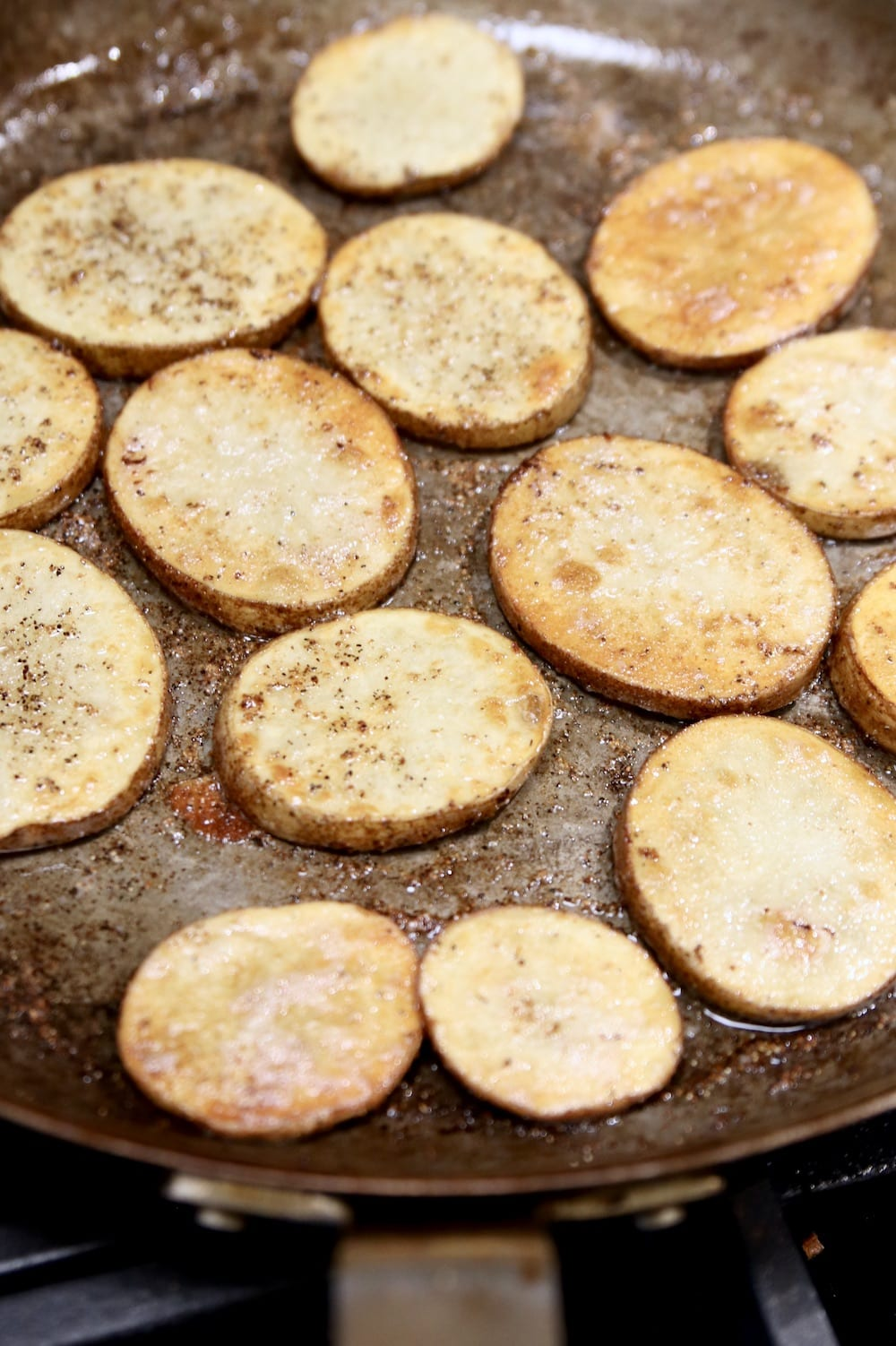 browned potato rounds in a skillet