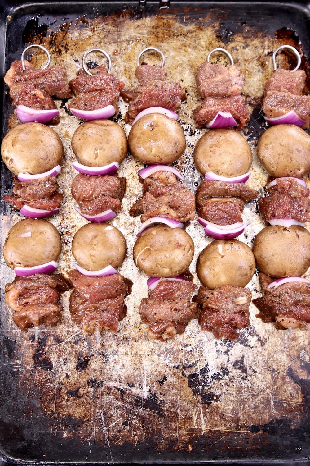 steak, mushroom and red onion kabobs on a sheet pan ready to grill