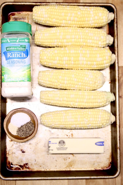 sheet pan with ears of corn, ranch dressing mix, seasonings, butter