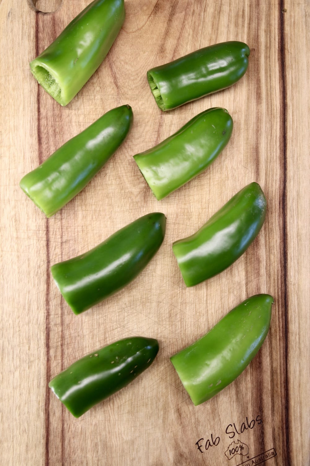 jalapeños with stems removed on a cutting board