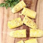 Chile Butter Corn on the Cob on a cutting board - cut in half with fresh parsley