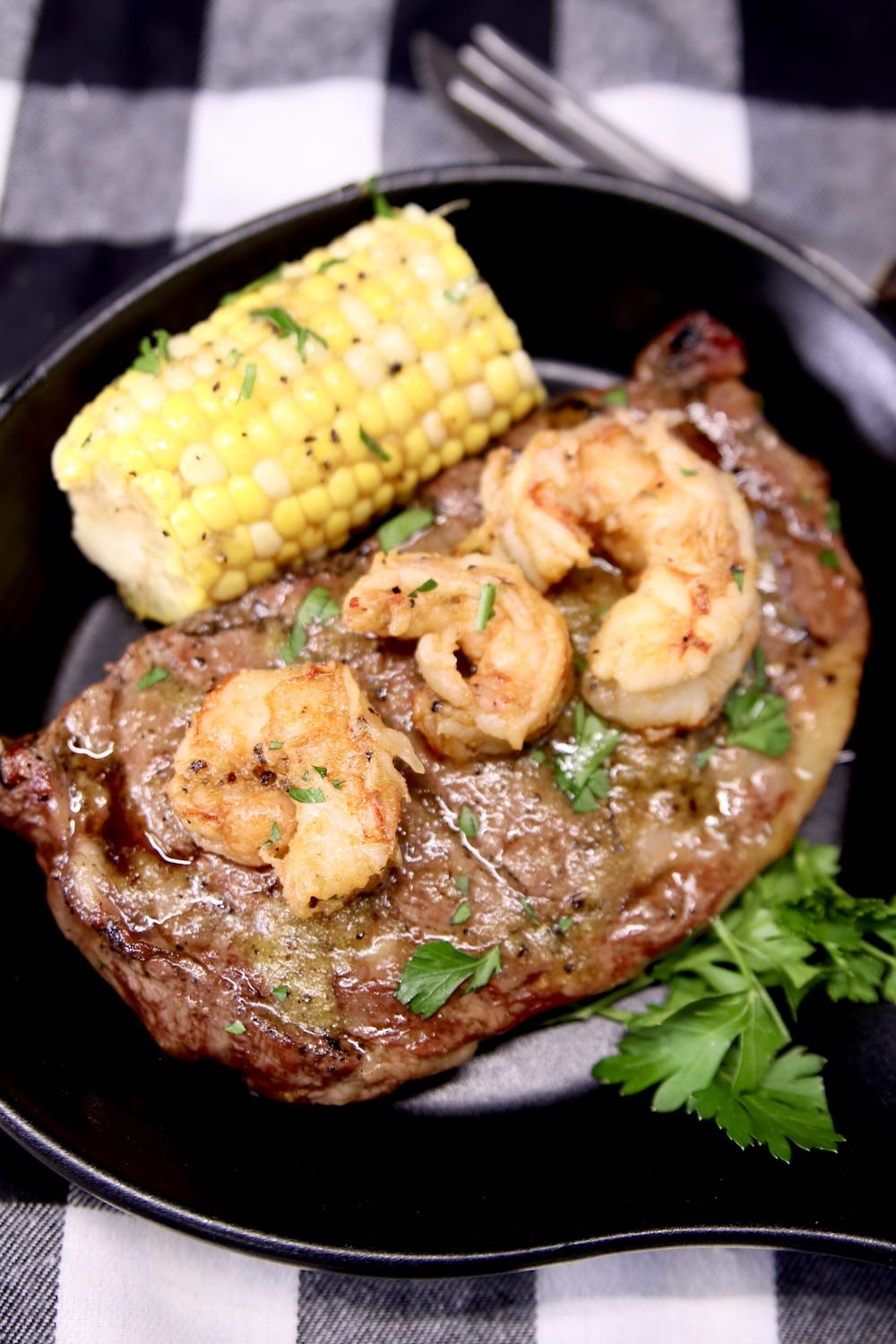 grilled steak, shrimp and corn on the cob on a black plate