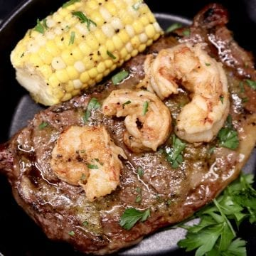 Grilled Ribeye Steak topped with 3 grilled shrimp, served with 1/2 corn on the cob and parsley garnish on a black plate