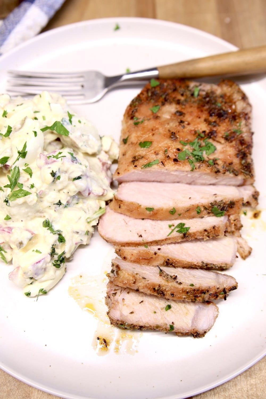 Partially sliced pork chop on a plate with potato salad