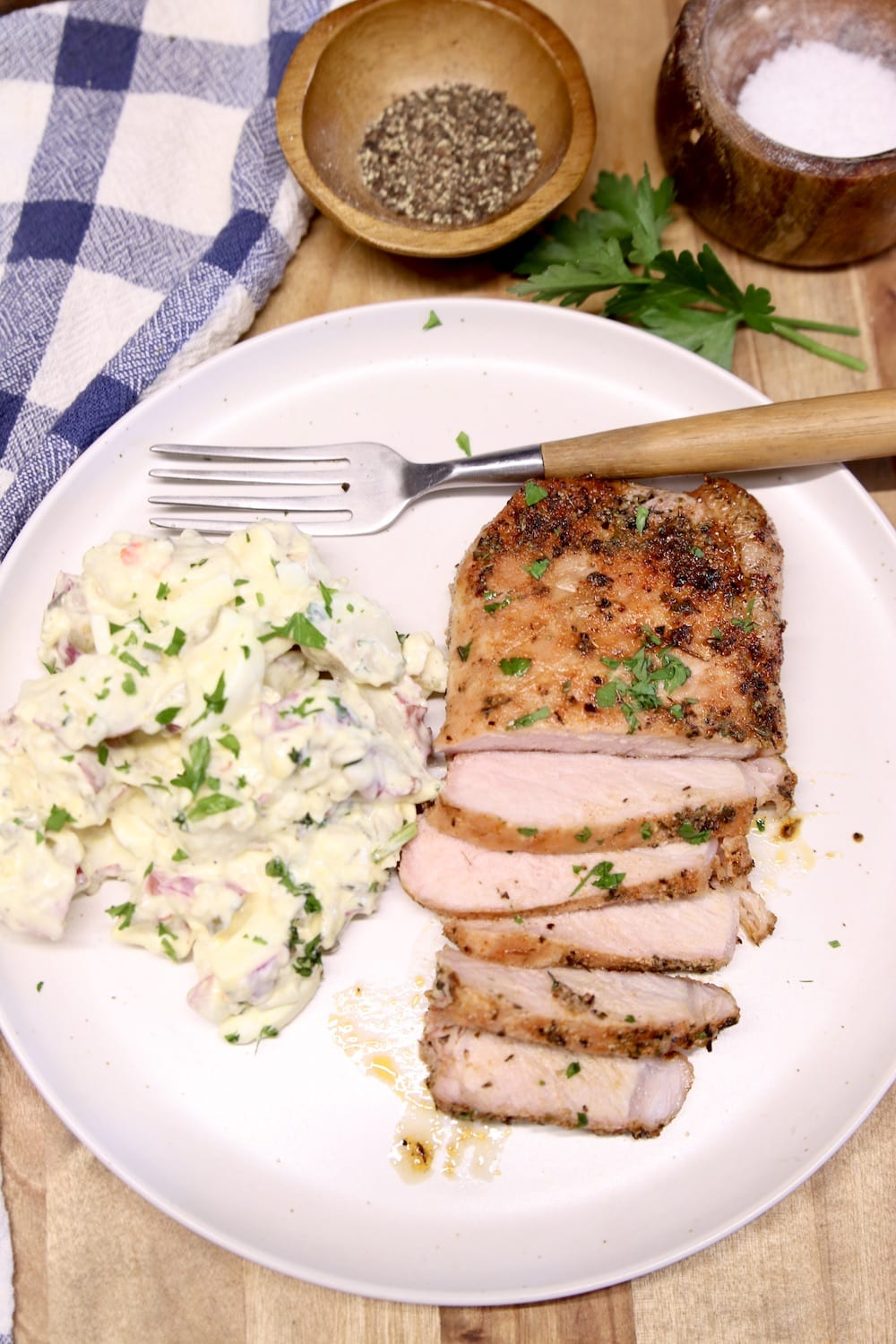Plate with a pork chop, partially sliced and potato salad, fork