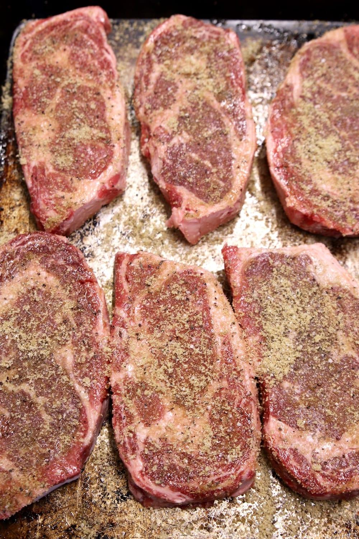 6 ribeye steaks seasoned with dry rub for grilling