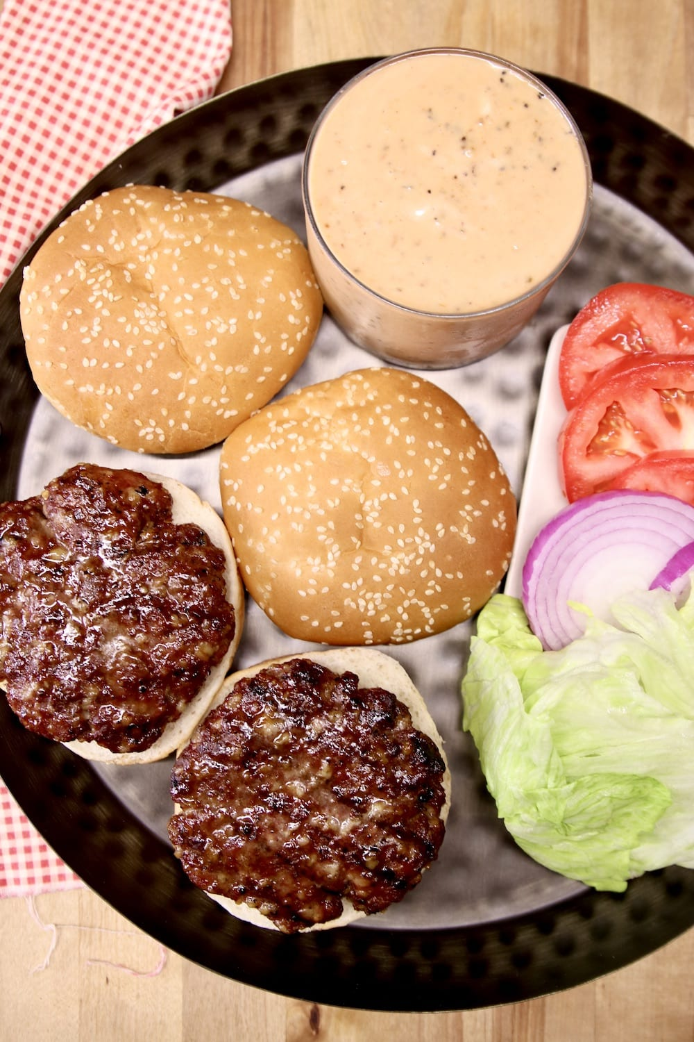 black platter with ground beef burgers, burger sauce, lettuce, tomato, onion