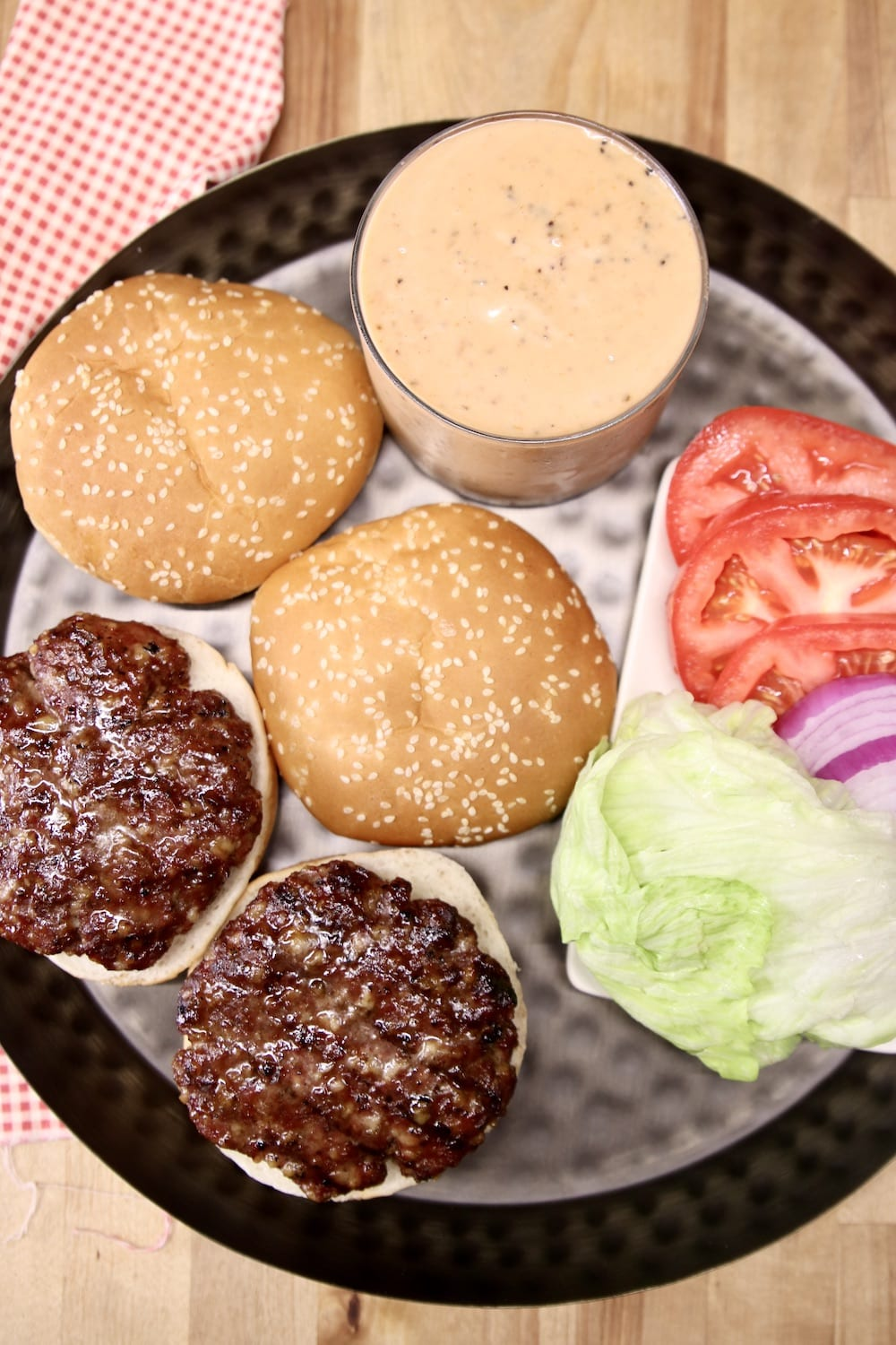 platter with 2 burger patties, buns, lettuce, tomato, onion and burger sauce