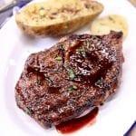 Ribeye Steak with Pomegranate Steak Sauce + 1/2 baked potato on a plate