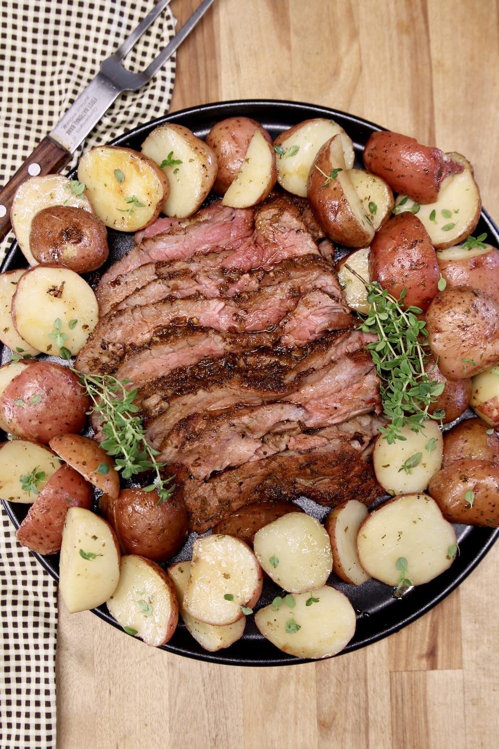 sliced roast beef on a platter with baby potatoes - overhead view
