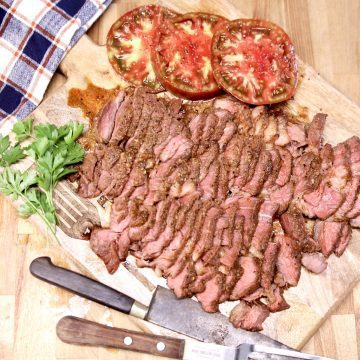 sliced roast beef on a cutting board with sliced tomatoes