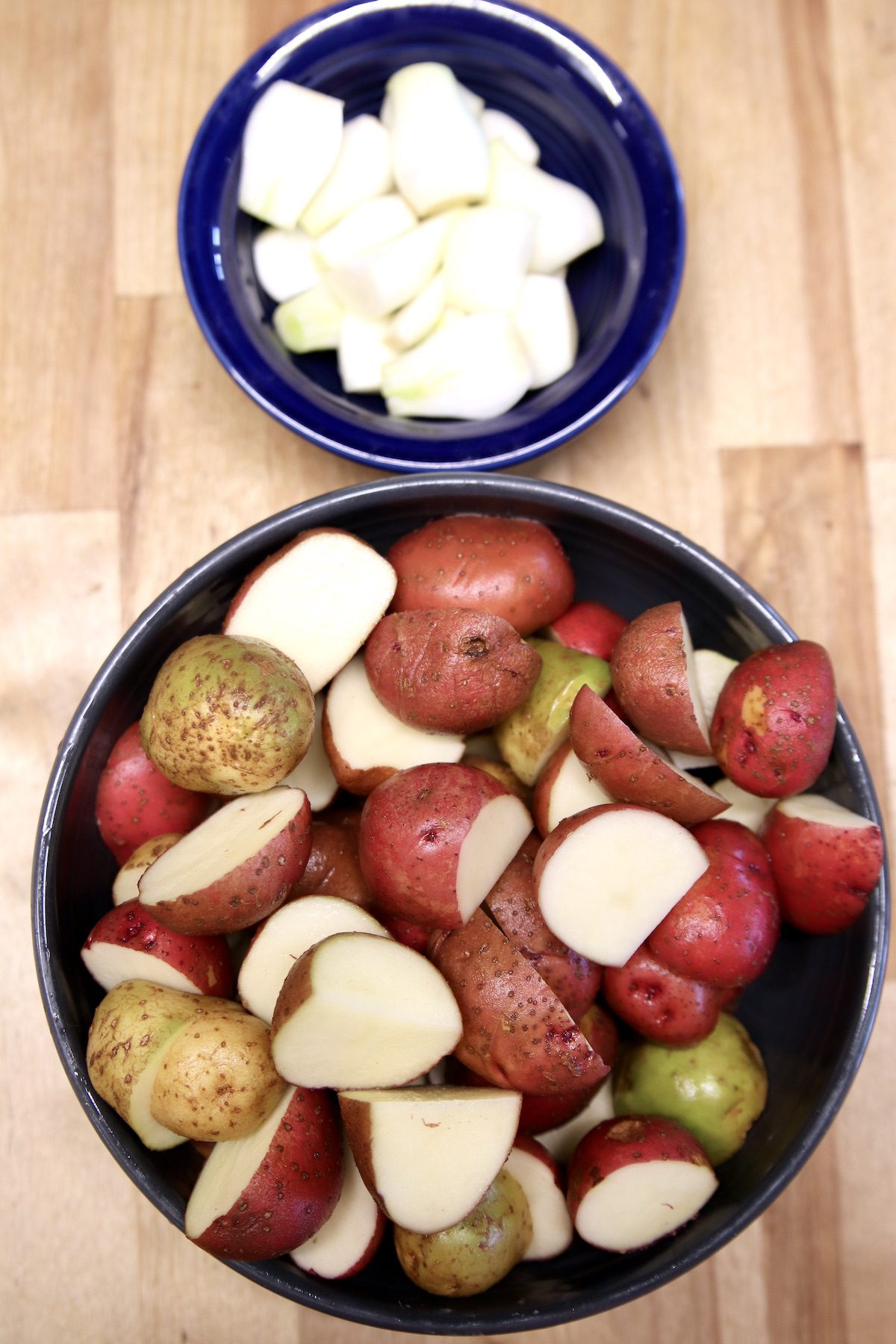 small bowl of onions, large bowl of cut up baby potatoes