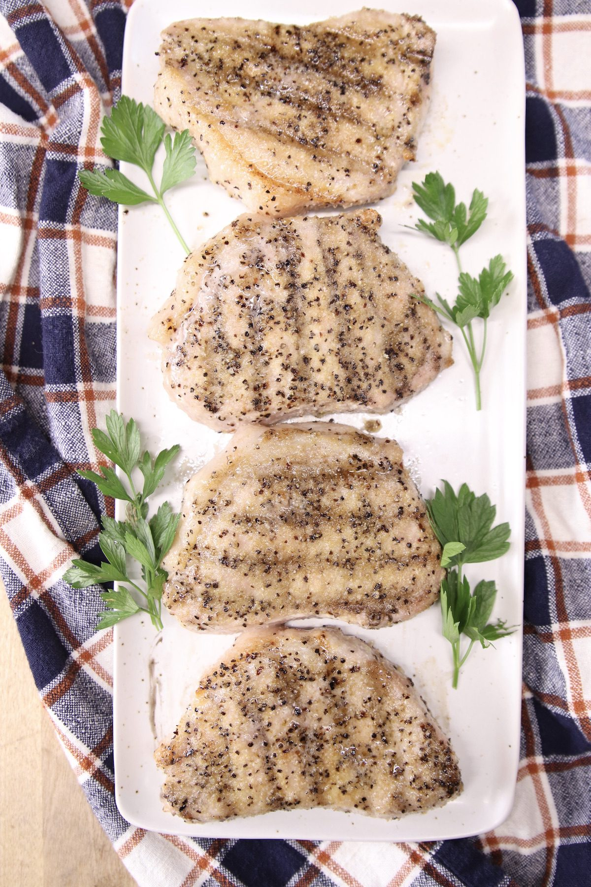 4 pork chops with grill marks on a white platter with fresh parsley