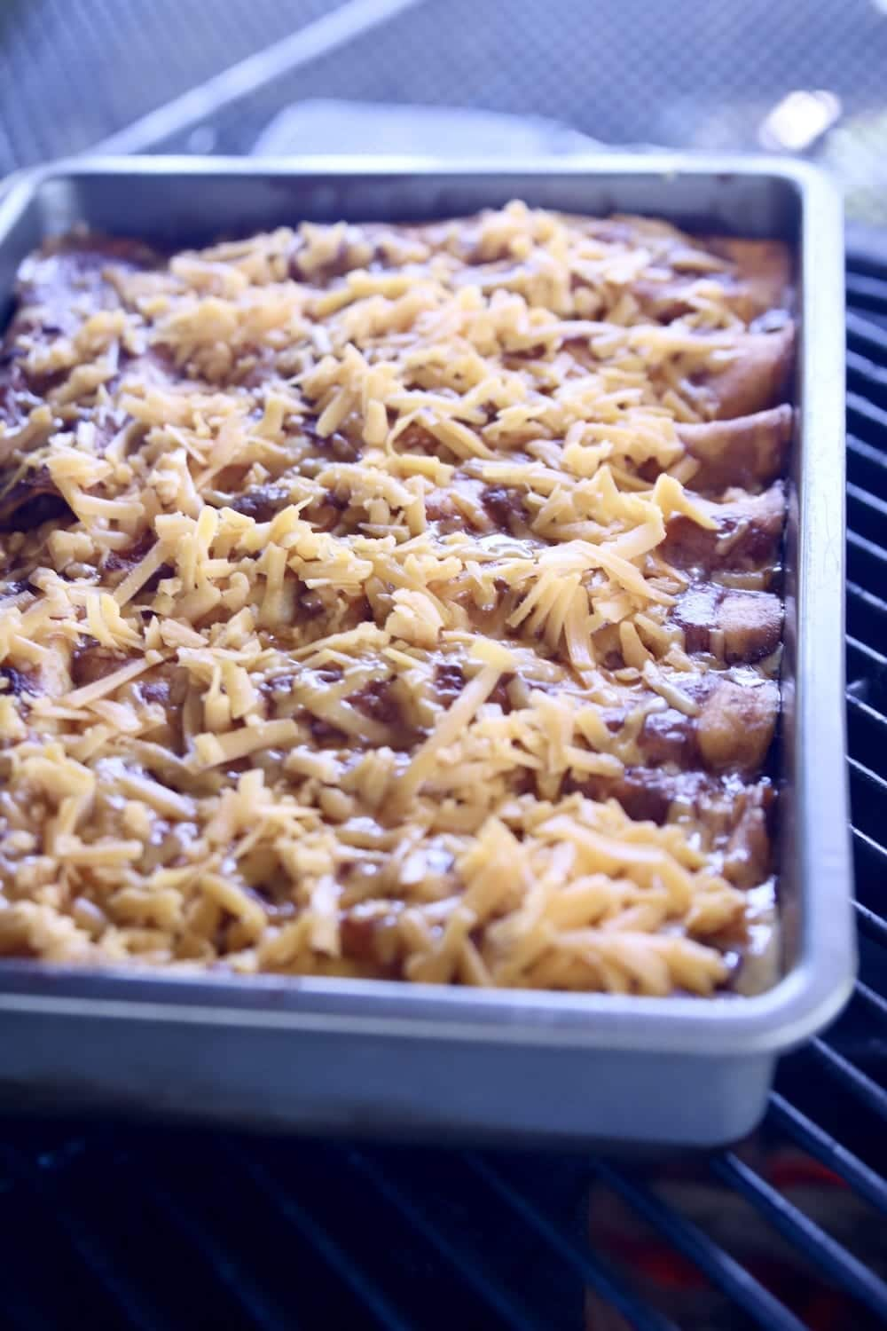 chicken enchiladas on a grill, topped with shredded cheese