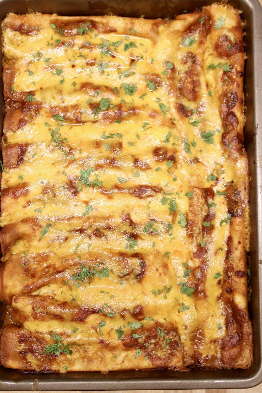 pan of chicken enchiladas with cilantro garnish