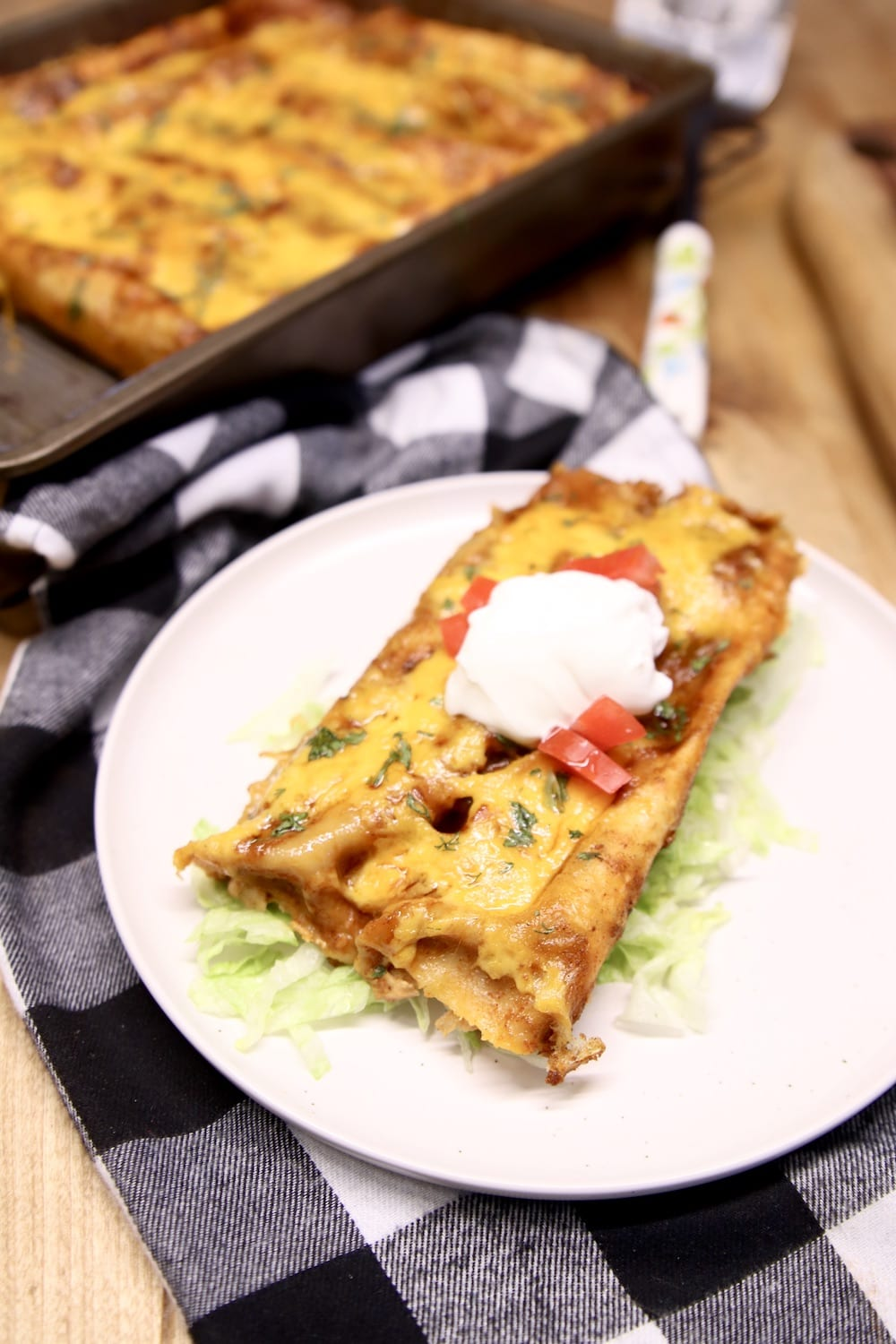 chicken enchiladas on a plate with sour cream
