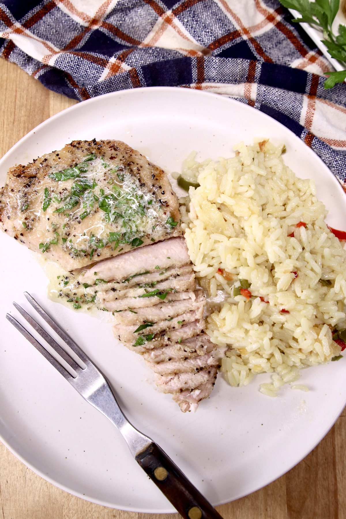 garlic butter pork chop on a plate, partially sliced with rice pilaf