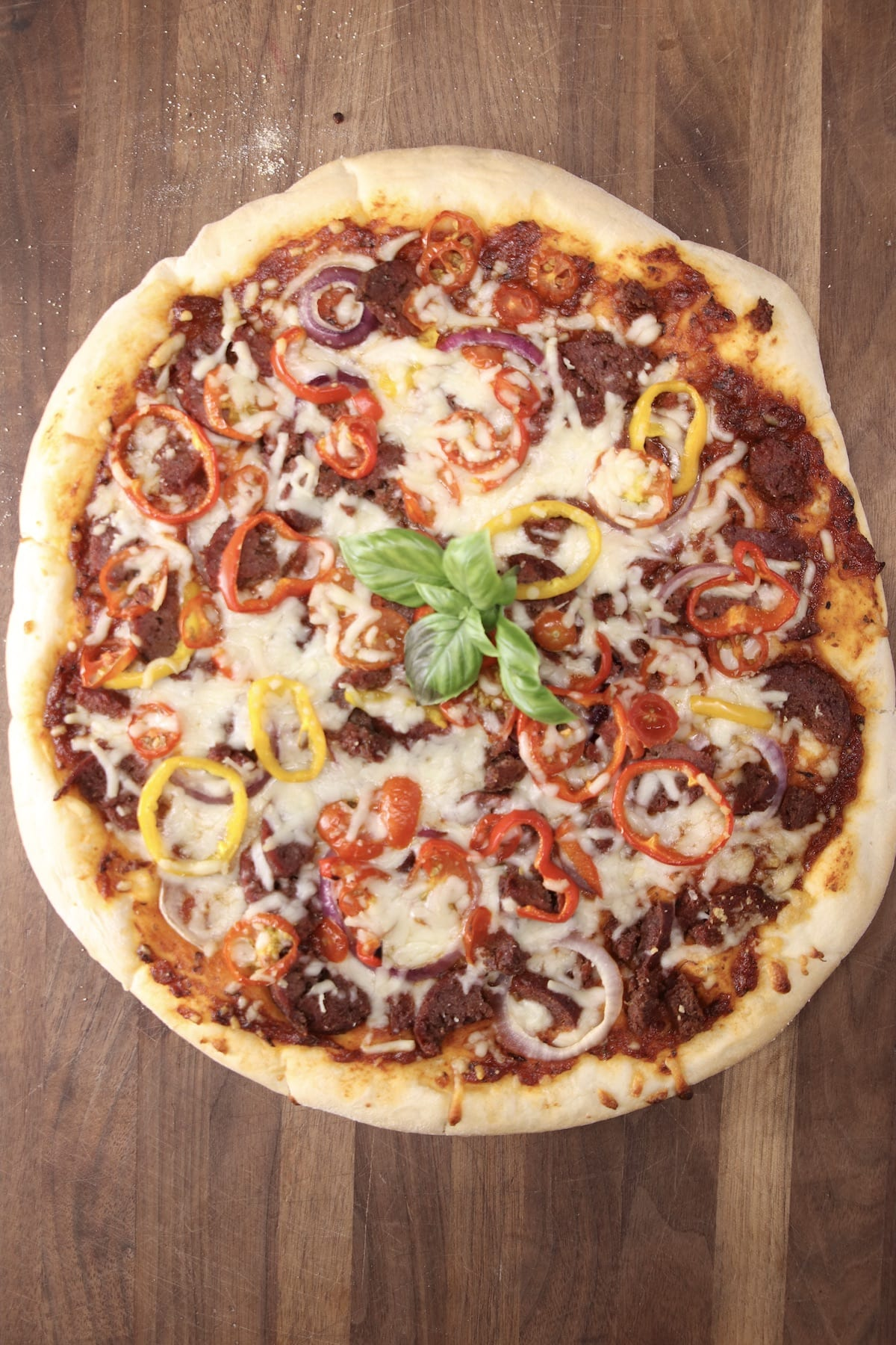 Grilled pizza with smoked sausage, peppers and onions