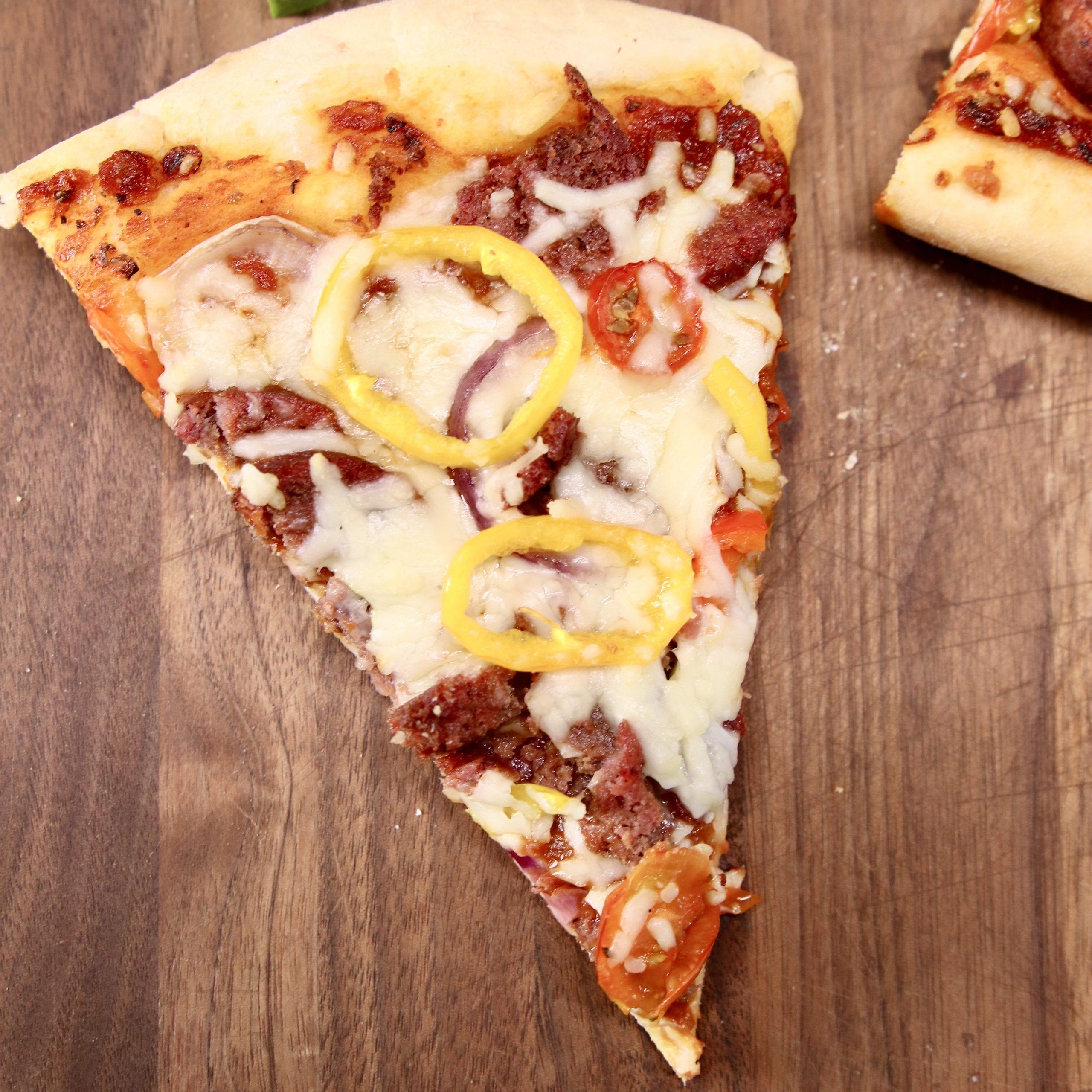 slice of pizza on a walnut cutting board