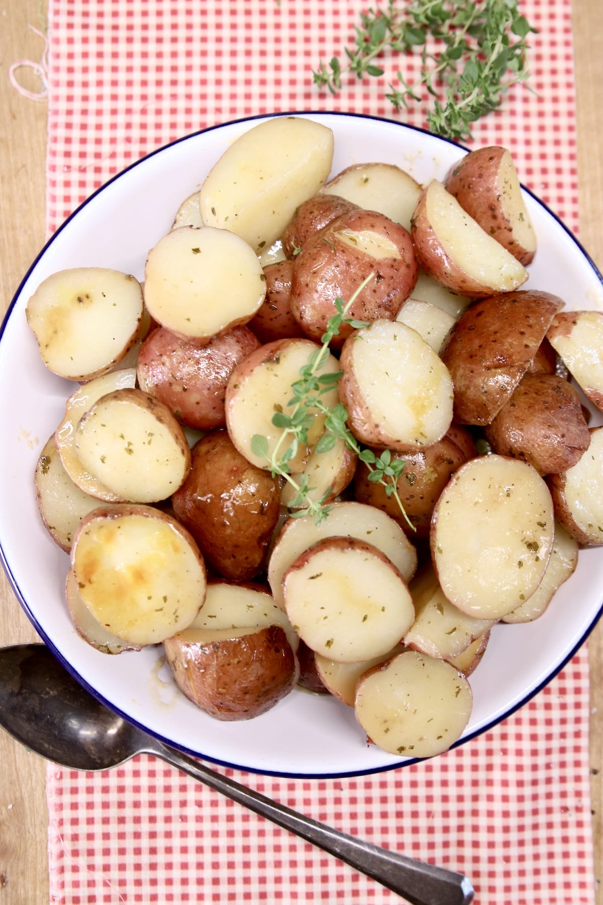 plate of cooked ranch baby potatoes on a red napkin with spoon