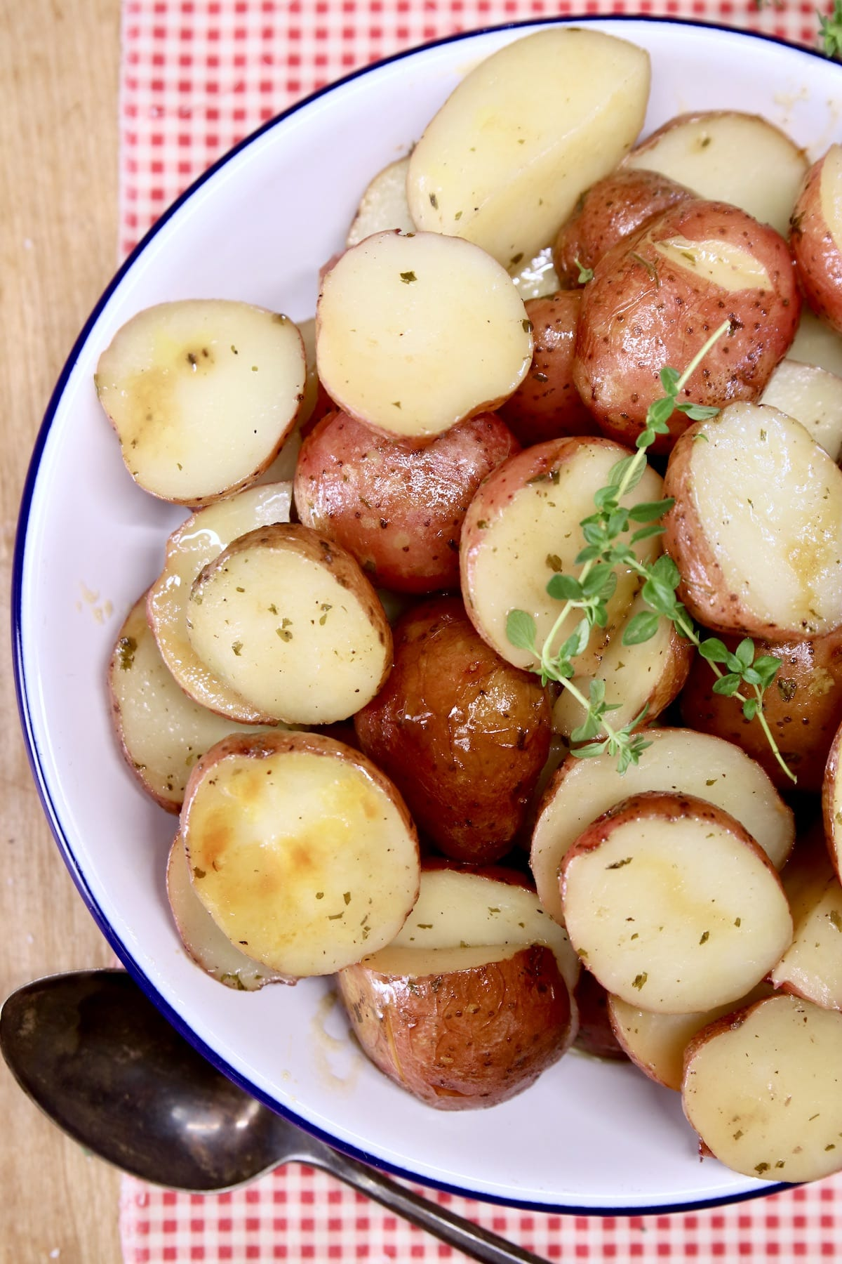 Bowl of baby red potatoes with thyme garnish