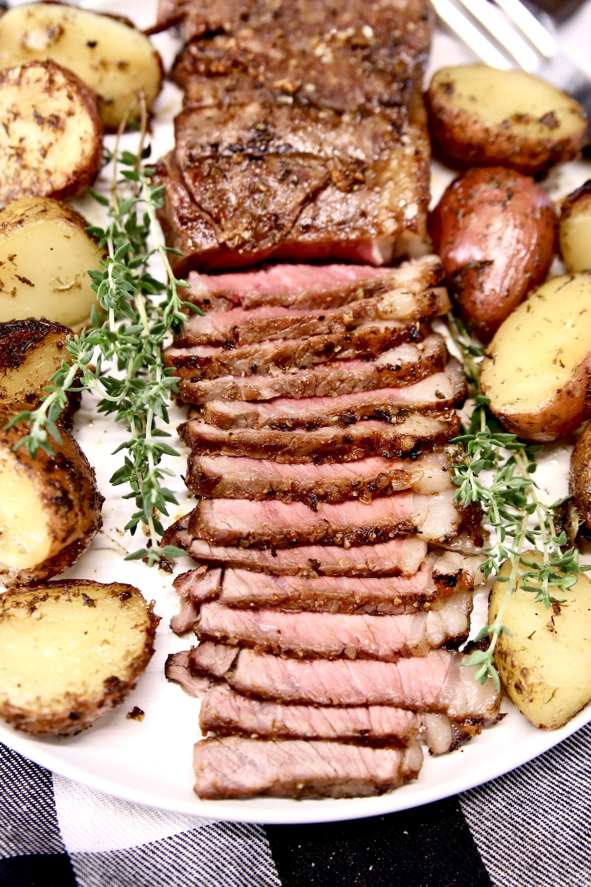 grilled NY Strip Steak sliced on a plate with potatoes