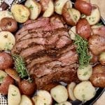 Grilled tri tip, sliced, surrounded by baby potatoes