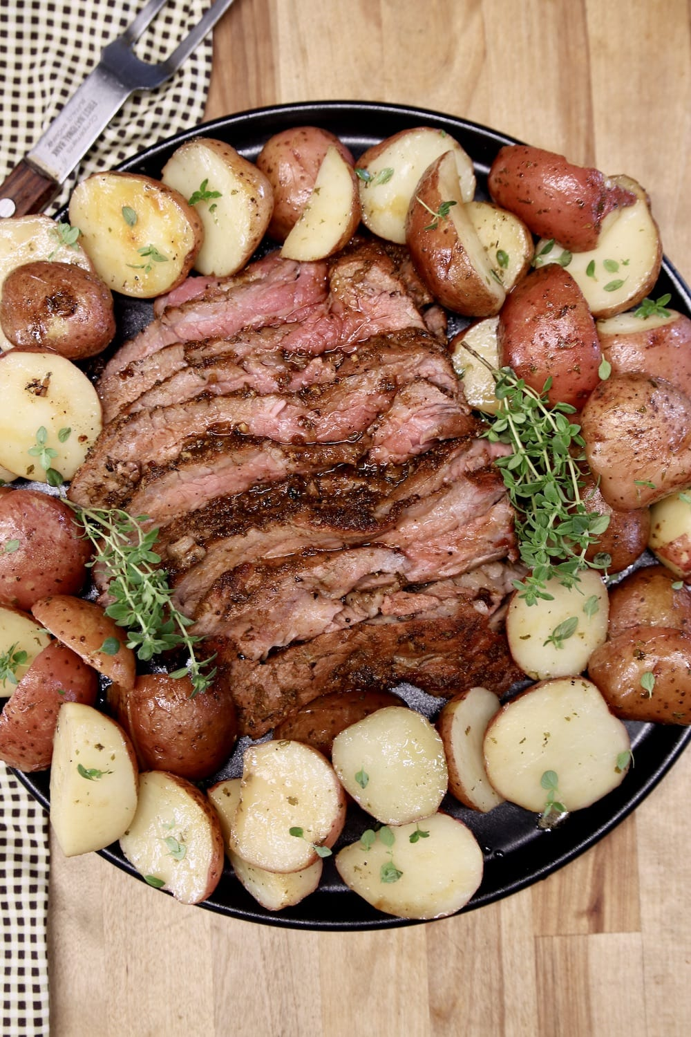 Grilled tri tip steak, sliced on a platter with potatoes