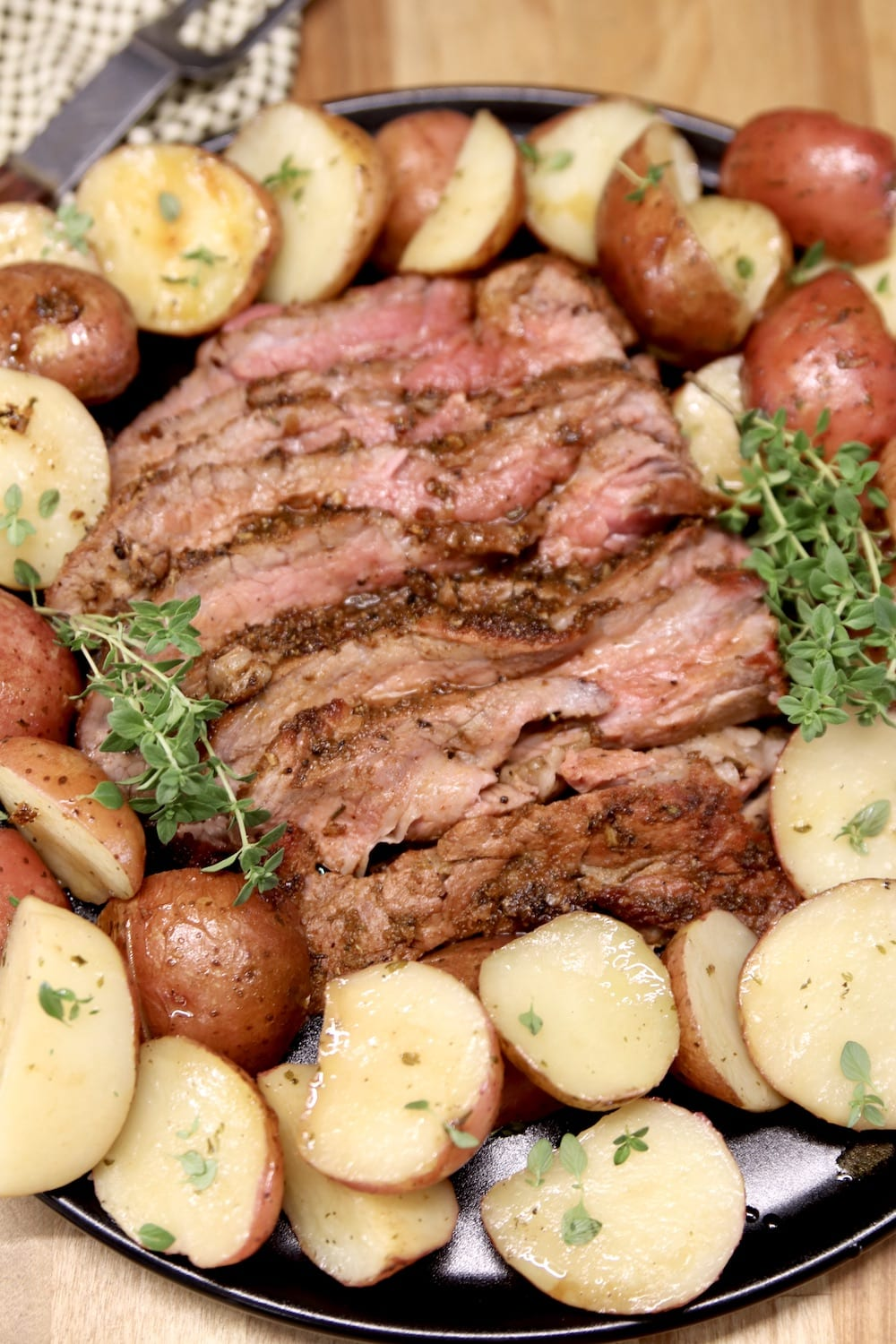 Grilled Tri-Tip sliced on a platter with baby potatoes, fresh thyme garnish